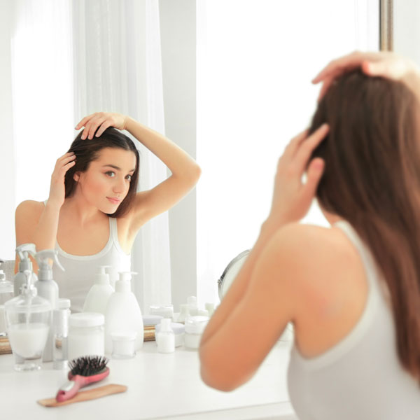 Donna controlla allo specchio perdita capelli
